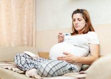 Femme enceinte s'asseyant sur le sofa avec le thermomètre photo stock