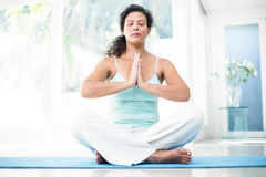 Femme enceinte s'asseyant sur le tapis d'exercice avec des mains jointives Photographie stock