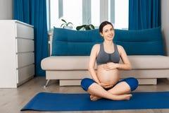 Femme enceinte s'asseyant sur le tapis de yoga Photos stock