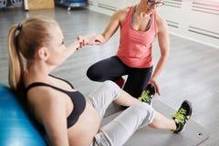 Femme enceinte s'asseyant sur le tapis et l'entraîneur personnel tenant son h photos libres de droits