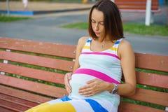 Femme enceinte s'asseyant sur un banc Photos libres de droits