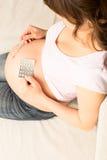 Femme enceinte s'asseyant sur un divan photographie stock libre de droits