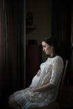 Femme enceinte s'asseyant sur une présidence photos stock