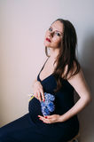 Femme enceinte s'asseyante regardant à l'appareil-photo Images libres de droits