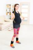 Femme enceinte s'exerçant à la maison Photo libre de droits