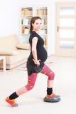Femme enceinte s'exerçant à la maison Photo stock