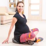 Femme enceinte s'exerçant à la maison Image stock