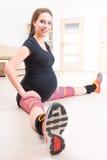 Femme enceinte s'exerçant à la maison Photos stock