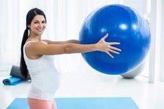 Femme enceinte s'exerçant avec la bille d'exercice Photographie stock libre de droits