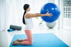 Femme enceinte s'exerçant avec la bille d'exercice Image stock
