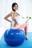 Femme enceinte s'exerçant sur la boule d'exercice Photo stock