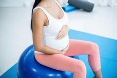 Femme enceinte s'exerçant sur la boule d'exercice Image stock