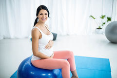 Femme enceinte s'exerçant sur la boule d'exercice Photos stock