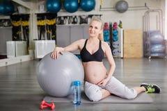 Femme enceinte sûre s'asseyant au gymnase avec la boule de pilates photos libres de droits