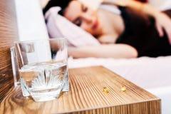 Femme enceinte se reposant avec des pilules actuelles images stock