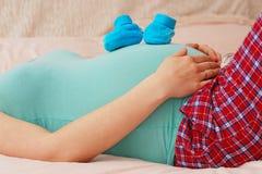 Femme enceinte se trouvant avec des chaussures de bébé sur son estomac Photo stock