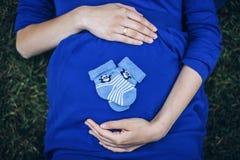 Femme enceinte se trouvant sur l'herbe tenant le ventre avec des chaussettes image stock