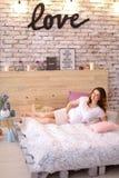 Femme enceinte se trouvant sur le lit dans la robe blanche, amour d'inscription sur le mur de briques Photo stock