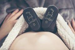 Femme enceinte se trouvant sur le sofa et tenant l'enfant à venir de chaussures Photos libres de droits