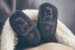 Femme enceinte se trouvant sur le sofa et tenant l'enfant à venir de chaussures Photographie stock