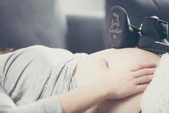 Femme enceinte se trouvant sur le sofa et tenant l'enfant à venir de chaussures Image libre de droits