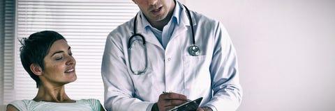 Femme enceinte se trouvant vers le bas parlant à son docteur photo stock