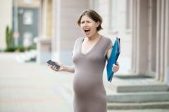 Femme enceinte soumise à une contrainte criant sur la rue Image stock
