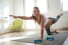 Femme enceinte sportive faisant des exercices à la maison Photos stock
