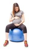 Femme enceinte sur une boule de stabilité photographie stock libre de droits