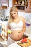 Femme enceinte tenant Apple vert et le sourire Photos stock