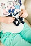 Femme enceinte tenant de petites chaussures de bébé Images libres de droits
