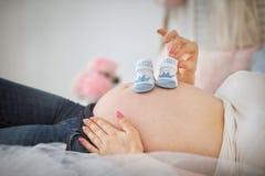 Femme enceinte tenant des butins de b?b? bleu photographie stock