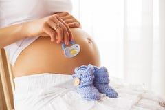 Femme enceinte tenant des chaussures de bébé et tétine Photographie stock
