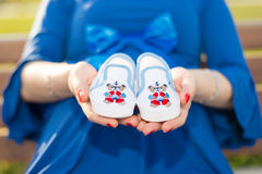 Femme enceinte tenant des espadrilles de bébé sur ses mains Photos stock
