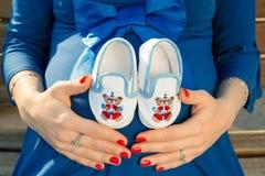 Femme enceinte tenant des espadrilles de bébé sur ses mains Photos libres de droits