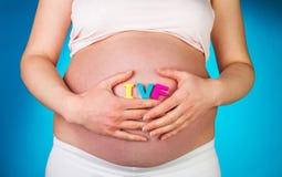 Femme enceinte tenant des mains dans le lettrage d'IVF sur le fond bleu Photos stock