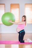 Femme enceinte tenant la boule d'exercice Images stock