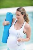 Femme enceinte tenant la bouteille d'eau et le tapis Images libres de droits