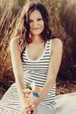Femme enceinte tenant le moulin à vent coloré sur le fond de forêt Photographie stock libre de droits