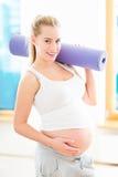 Femme enceinte tenant le tapis de yoga Photographie stock libre de droits