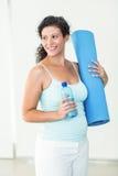 Femme enceinte tenant le tapis et la bouteille d'eau d'exercice Photographie stock libre de droits