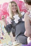 Femme enceinte tenant les vêtements artificiels de bébé Image libre de droits