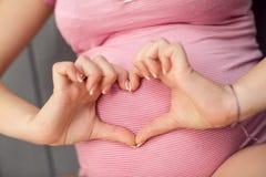 Femme enceinte tenant ses mains dans la forme de coeur sur la bosse de bébé Photo stock