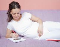Femme enceinte tenant son ventre et écrivant des notes Photo stock