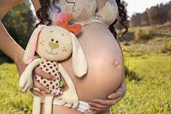 Femme enceinte tenant un jouet Photos libres de droits