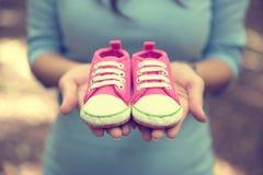 Femme enceinte tenant une paire de chaussures roses d'enfant en bas âge d'espadrilles Photo stock
