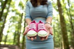 Femme enceinte tenant une paire de chaussures roses d'enfant en bas âge d'espadrilles Photographie stock