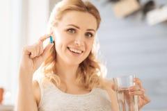 Femme enceinte tenant une pilule et un verre de l'eau images stock