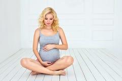 Femme enceinte touchant son ventre avec des mains Photo libre de droits