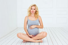Femme enceinte touchant son ventre avec des mains Photo stock